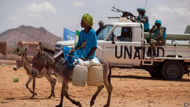 A man rides his donkey past UN troops standing guard at a camp for internally displaced people  in South Darfur, Sudan, June 2014
