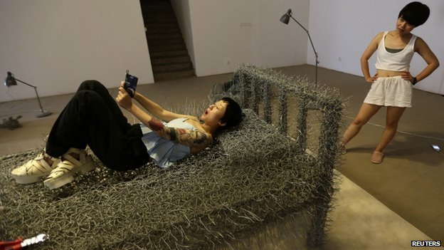 A woman watches as another takes a selfie on a iron wire bed at Beijing Art Now Gallery.