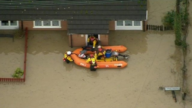 An RNLI rescue team at the door of a flooded home