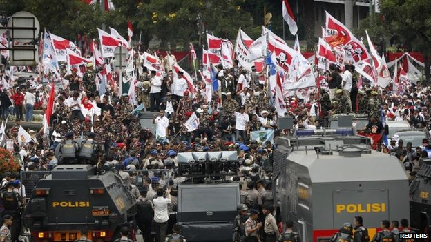 Supporters of losing presidential candidate Prabowo Subianto rally in front of a police blockade outside the Constitutional Court in Jakarta, 21 August 2014