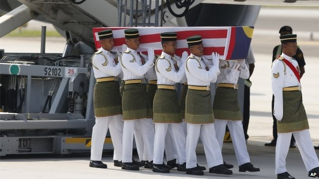 Malaysian Army soldiers carry a coffin containing one of the bodies of the downed MH17 flight upon arrival at Kuala Lumpur International Airport in Sepang, Malaysia, Friday, 22 August 2014