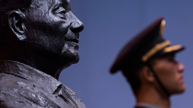 A soldier stands in front of a sculpture featuring former Chinese leader Deng Xiaoping during the Exhibition of the 110th anniversary of the birth of Deng Xiaoping on 21 August, 2014 in Hong Kong