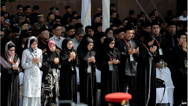 Family members and next-of-kin of the Malaysia Airlines flight MH17 victims pause for a moment of silence during a ceremony in the Bunga Raya complex at Kuala Lumpur International Airport in Sepang on 22 August  2014.
