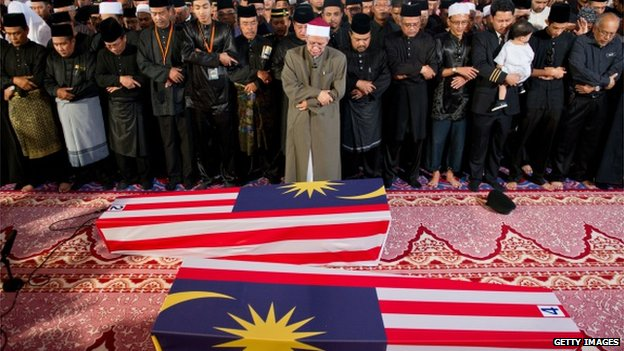 Malaysian Muslim and family members offer special prayers for the remains of co-pilot Ahmad Hakimi Hanapi (L) and flight attendant Nur Shazana Mohamed Salleh (R), the Malaysians who perished aboard flight MH17 that was downed in eastern Ukraine at a mosque in Putrajaya, outside Kuala Lumpur on 22 August 2014