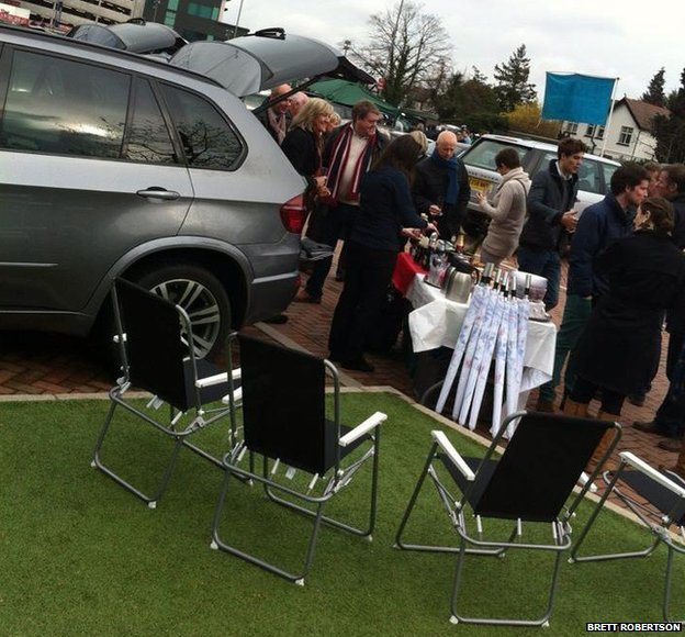 A car park picnic with umbrellas, Range Rovers and deck chairs