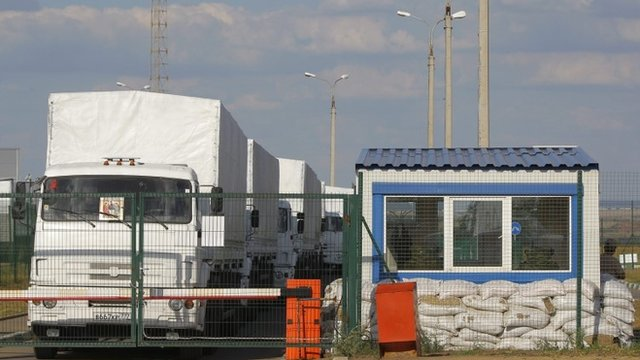 A Russian aid convoy of white trucks waits to enter Ukraine at a border control point
