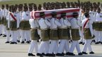 Coffins draped in the national flag were slowly carried to waiting hearses