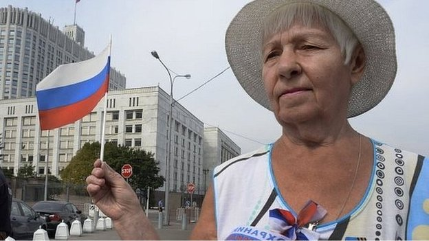 A woman waves a Russian flag in front of the parliament building in Moscow on National Flag Day (22/08/14)