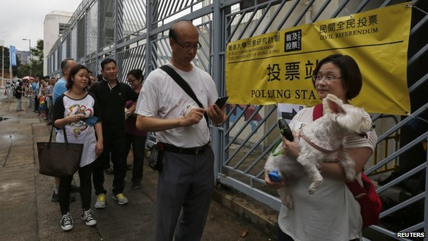 A voter carries her dog as she joins others lining up outside a polling station during an unofficial referendum in Hong Kong June 22, 2014.