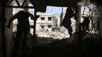 A Palestinian walks inside a house, which witnesses say was hit by an Israeli air strike