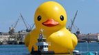 "The six-story tall ""Rubber Duck"" by Dutch artist Florentijn Hofman leads a procession of Tall Ships into Los Angeles harbour in San Pedro, California on August 20"