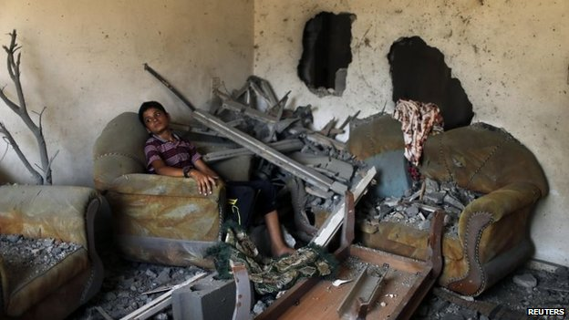 A Palestinian boy sits in his family's house, which witnesses said was damaged in an Israeli air strike