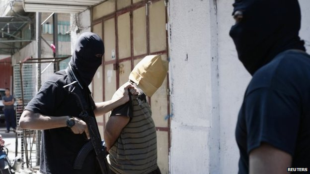 A Hamas militant grabs a Palestinian suspected of collaborating with Israel