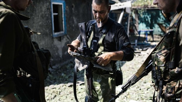 A pro-Russian gunman holds a piece of shrapnel from a rocket after shelling in Donetsk on 22 August 2014