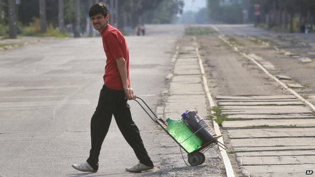 A local citizen pulls a cart with water in the city of Luhansk, eastern Ukraine (22 August 2014)