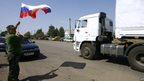 Man holds Russian flag as lorry crosses border