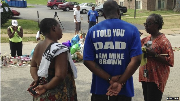 Michael Brown Sr., talks with well-wishers at a makeshift memorial set up to honour his son, Michael, who was fatally shot by a white police officer 13 days ago in Ferguson