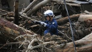 A policeman searches for survivors at a site where a landslide swept through a residential area at Asaminami ward in Hiroshima (23 August 2014)