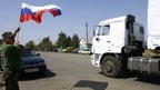 A local resident holds a Russian national flag as lorries, part of a Russian humanitarian convoy, cross the Ukrainian border on 22 August 2014