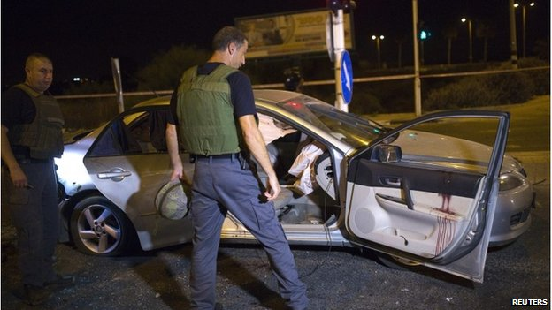 An Israeli policeman surveys the scene in the southern city of Gan Yavne after it was hit by a rocket on 22 August.