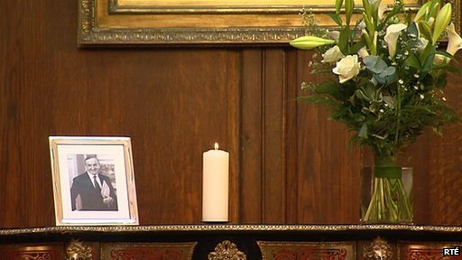 A candle burns beside a photograph of the former taoiseach inside Mansion House