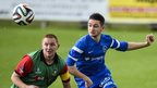 Glentoran's Stephen McAlorum and Ballinamallard's Liam Martin keep their eyes on the ball at Ferney Park