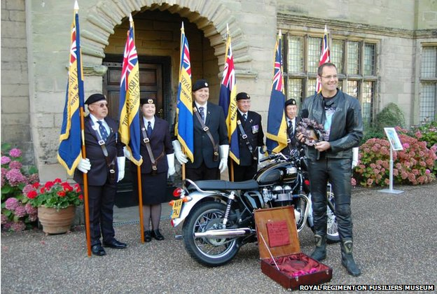 Veterans holding standards and a motorcyclist with a wreath