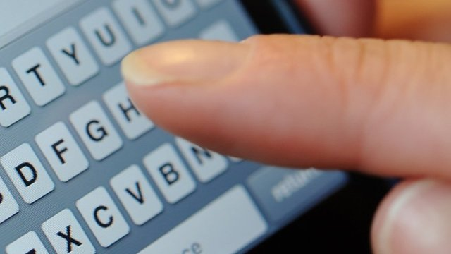 Person typing a text message on a phone