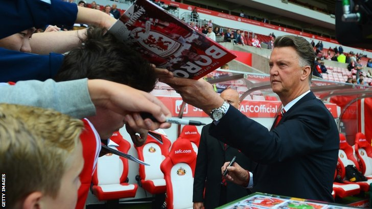 Manager Louis van Gaal of Manchester United signs autographs