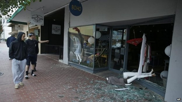 People walk past a tumbled mannequin and broken storefront window in Napa