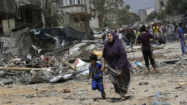 A Palestinian mother and her son flee from their home as Israeli planes targeted a house in Gaza City (24 August 2014)