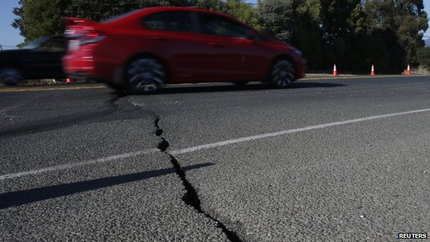 A car drives over cracked asphalt along Highway 12 after a 6.0 earthquake in Napa, California (24 August 2014)