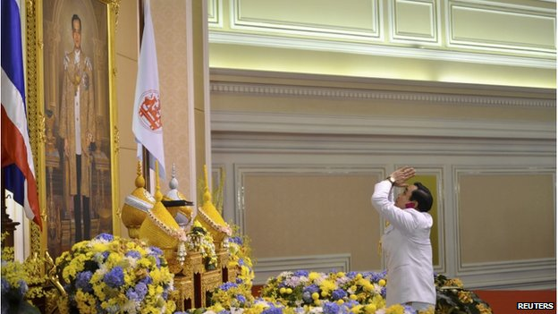 Thailand's newly appointed Prime Minister Prayuth Chan-ocha pays his respects as he receives the royal endorsement, in front of a portrait of Thai King Bhumibol Adulyadej, at the Royal Army headquarters in Bangkok in this 25 August 2014 handout photo provided by the Thailand Government House