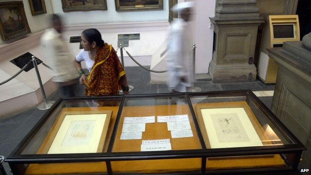 Indian visitors walk past displays of two artworks by Salvador Dali in Durbar Hall of The Victoria Memorial in Kolkata on August 14, 2014