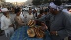 Afghans buy bread at a busy market in Kabul June, 2014