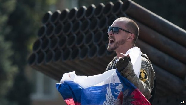 A pro-Russian rebel displays a flag in central Donetsk, 24 Aug