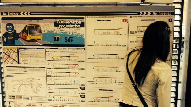 A woman looks at the map of the Transmilenio bus lines in Bogota