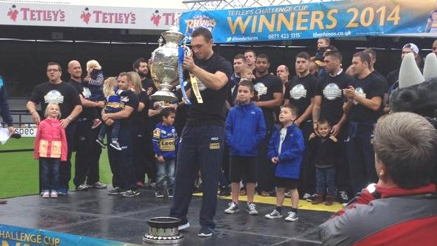 Leeds Rhino playing lifting a trophy with teammates behind him