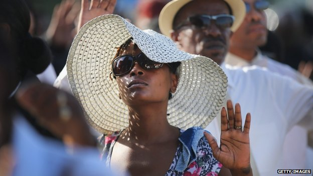 Guests raise their hands as they stand in line for the funeral of Michael Brown.