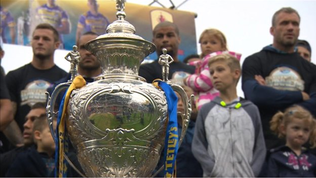 Trophy in front of Leeds Rhinos players