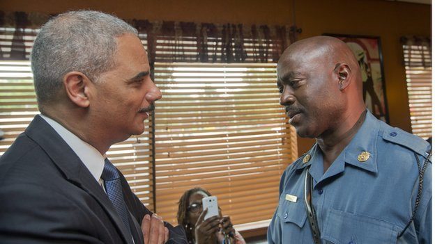 US Attorney General Eric Holder (L) talks with Capt. Ron Johnson, right, of the Missouri State Highway Patrol