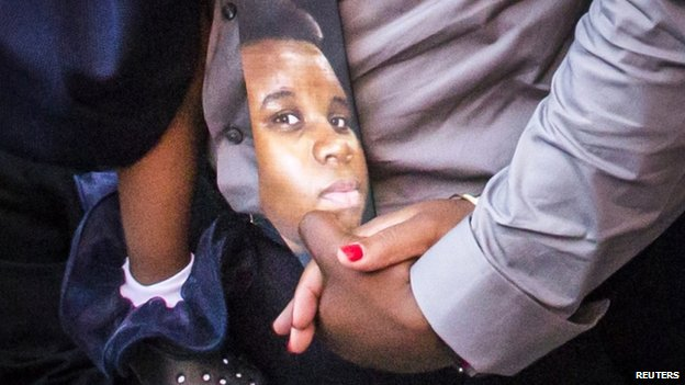 Michael Brown is seen on a tie worn by his father during the funeral