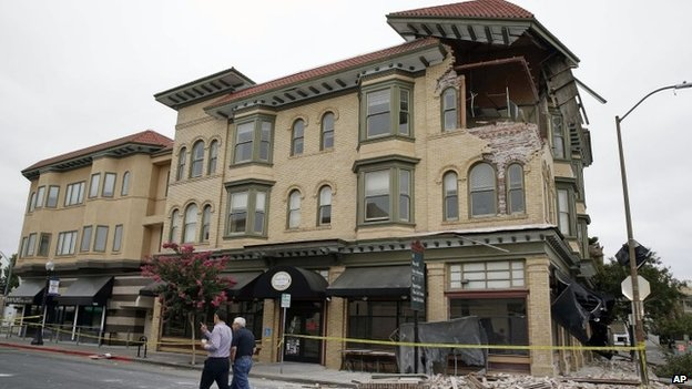 Two men walk past the earthquake-damaged building that housed the Carpe Diem wine bar Napa, California 25 August 2014