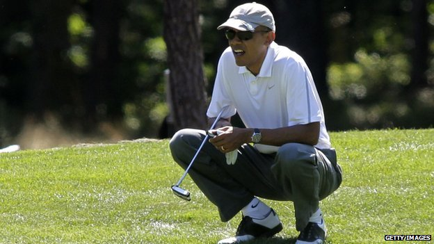 President Barack Obama squats by a golf course green.