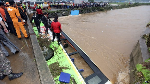 In a photo taken on 25 August, 2014, South Korean rescue workers attempt to secure a bus submerged by floodwaters in the south-eastern town of Changwon