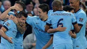 Man City players celebrate Sergio Aguero (far left) scoring their third goal against Liverpool
