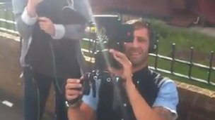 A cameraman films BBC reporter Andy Bell