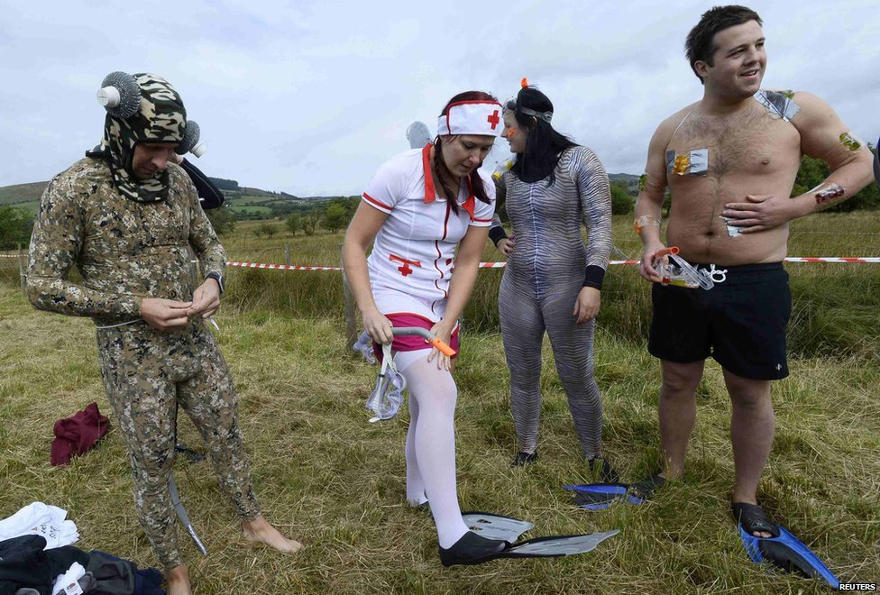 Llanwrtyd Wells bog snorkelling championships 2014 - competitors adjust their costumes