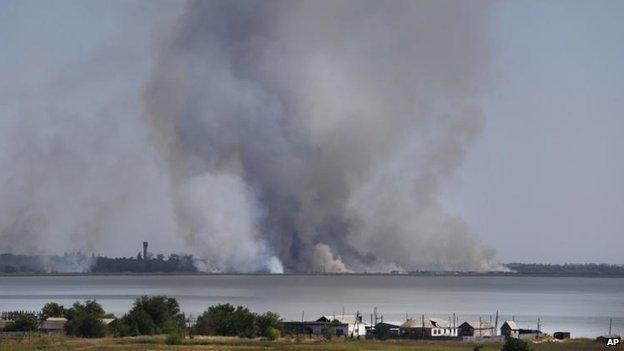 Smoke rises close to the town of Novoazovsk, 26 Aug
