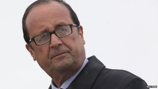 French President Francois Hollande delivers a speech in the rain on the Ile de Sein, an island located near the Pointe-du-Raz, off the Brittany coast, on 25 August 2014.